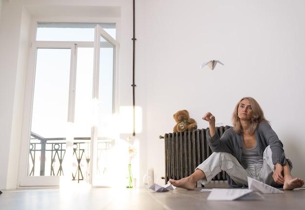 Une femme assise sur le sol de son appartement en état de prostration a lancé un avion en papier