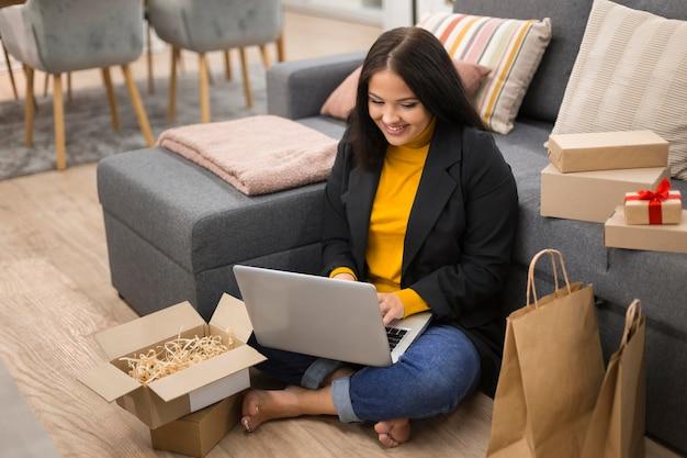 Femme assise sur le sol avec son ordinateur portable sur ses genoux