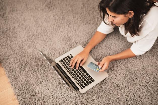 Femme assise sur le sol et travaillant sur un ordinateur portable