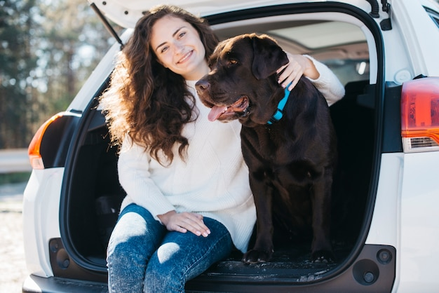 Femme assise avec son chien dans le coffre ouvert