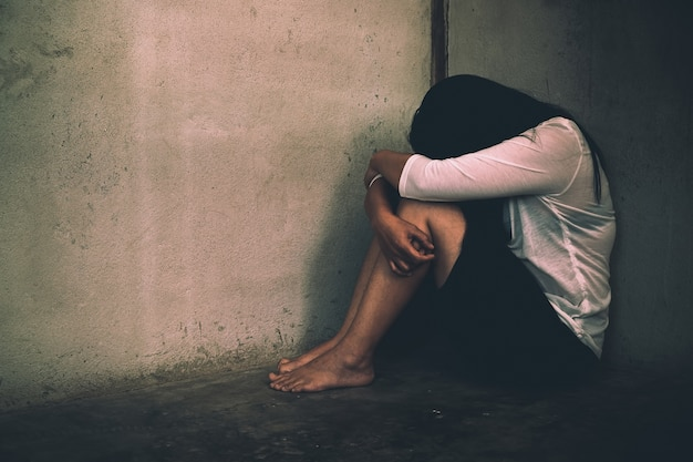 Femme assise souche, malheureuse dans la salle, la violence domestique, les abus et les gens.