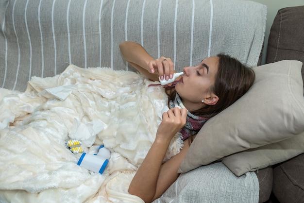Femme assise sous la couverture au lit malade sur la grippe des infections saisonnières