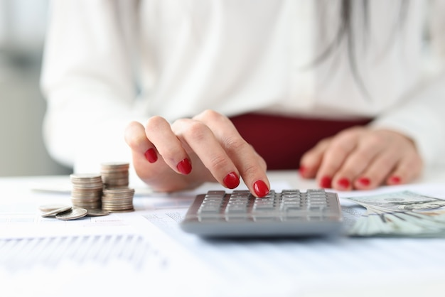 Femme assise à table avec de l'argent et comptant sur la calculatrice