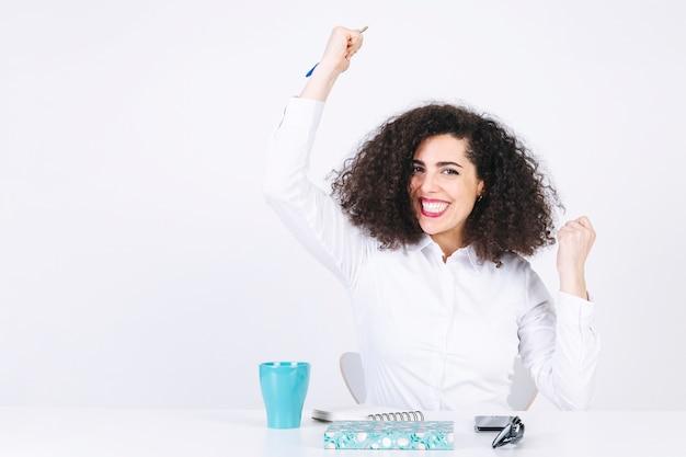 Femme assise à table et célébrant le succès