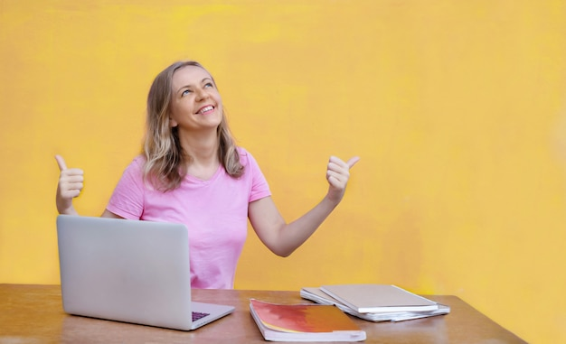 Femme assise à table avec ordinateur portable et montrant les pouces vers le haut sur fond jaune