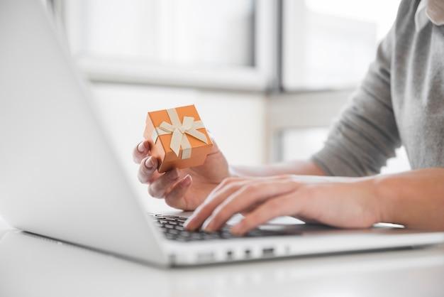 Femme assise à table avec ordinateur portable