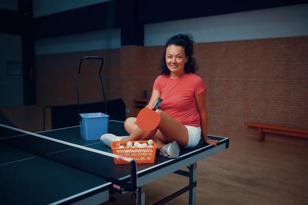 Femme assise sur une table de ping-pong