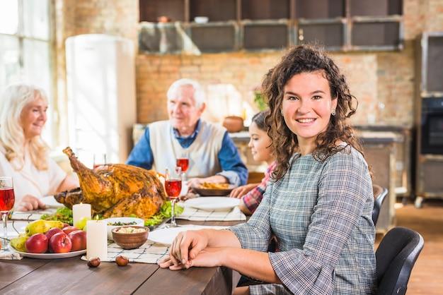Femme assise à table près d'une fille et des personnes âgées