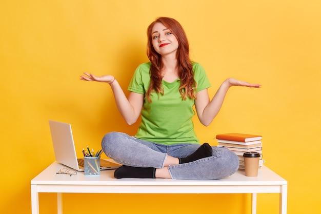 Femme assise sur une table près de l'ordinateur portable