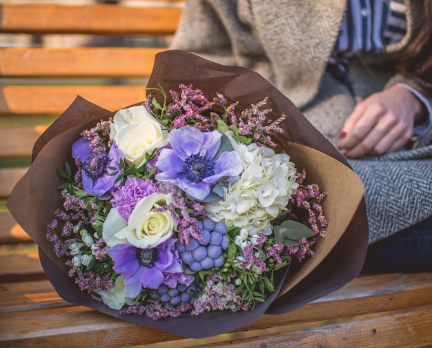 Femme assise à la table de repos avec un bouquet de fleurs en papier.
