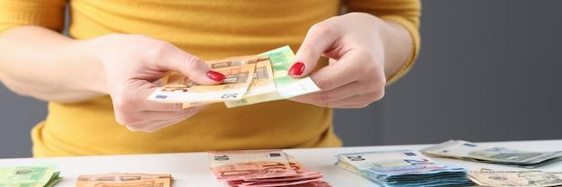 Femme assise à table et tenant des billets en euros dans ses mains en gros plan. notion de comptabilité