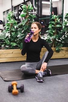 Femme assise sur un tapis d'exercice l'eau potable