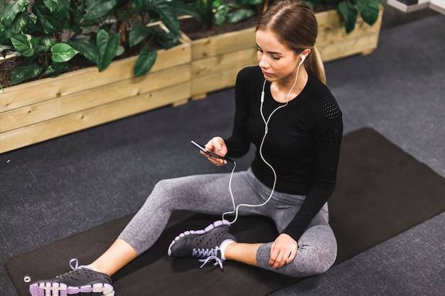 Femme assise sur un tapis d'exercice en écoutant de la musique