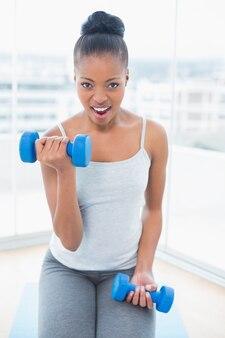 Femme assise sur un tapis d'exercice avec haltère