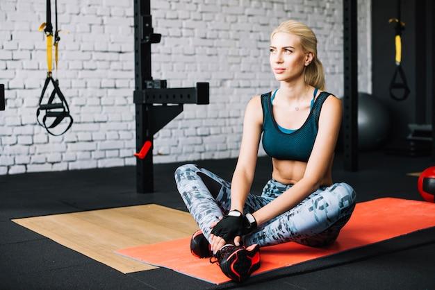 Femme assise sur un tapis extensible
