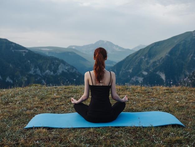 Femme assise sur des tapis de fitness et médite le yoga asana à l'extérieur dans les montagnes