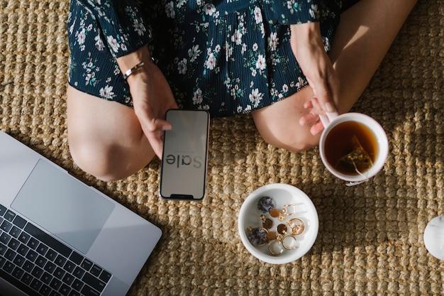 Femme assise sur un tapis en osier à l'aide d'un téléphone mobile