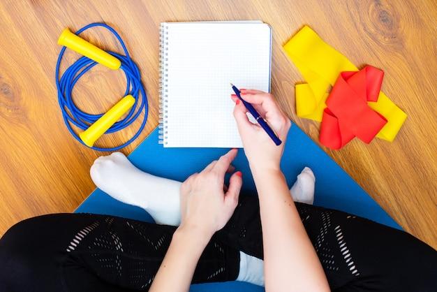 Femme assise sur un tapis de yoga écrit avec un stylo dans un cahier vide.