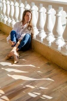Femme assise à la terrasse et allongée, journée ensoleillée. jeune femme habillée en chemise blanche et denim bleu