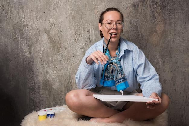 Femme assise avec toile et pinceau sur marbre . photo de haute qualité