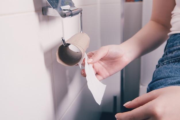 Femme assise sur les toilettes avec rouleau de serviette sur le point de se terminer