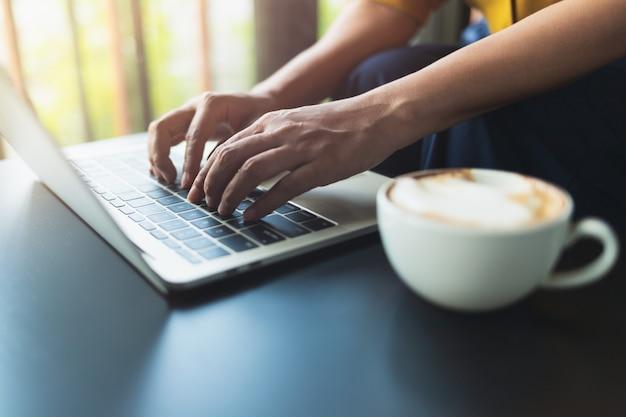 Femme assise en train de taper un bouton sur le portable sur une table en bois noire