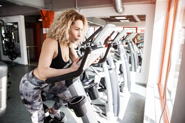 Une femme assise sur un vélo d'exercice. elle a hâte.