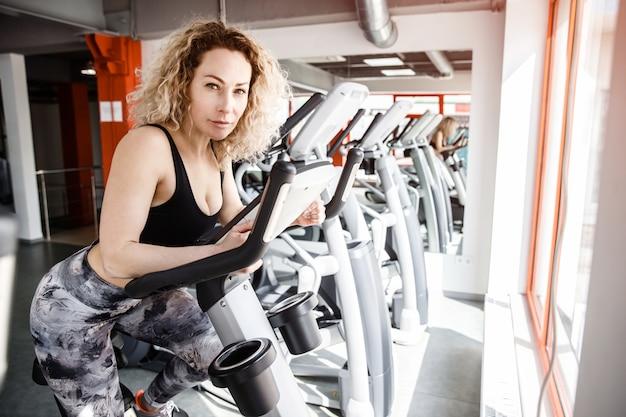 Une femme assise sur un vélo d'exercice. elle regarde la caméra.
