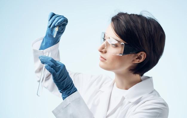 Femme assistant de laboratoire avec une fiole dans ses mains, des lunettes sur son visage et une blouse médicale.