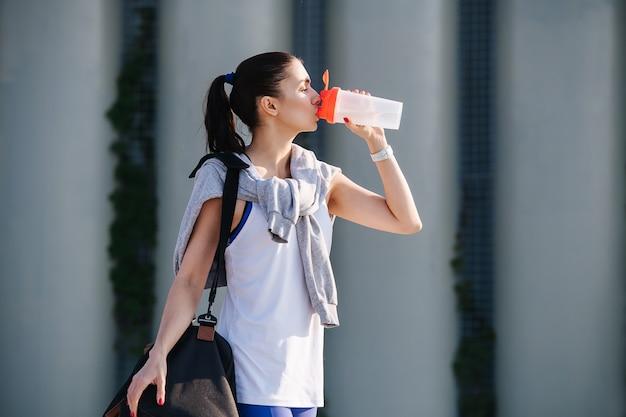 Femme assoiffée en tenue sportive debout dans la rue de l'eau potable