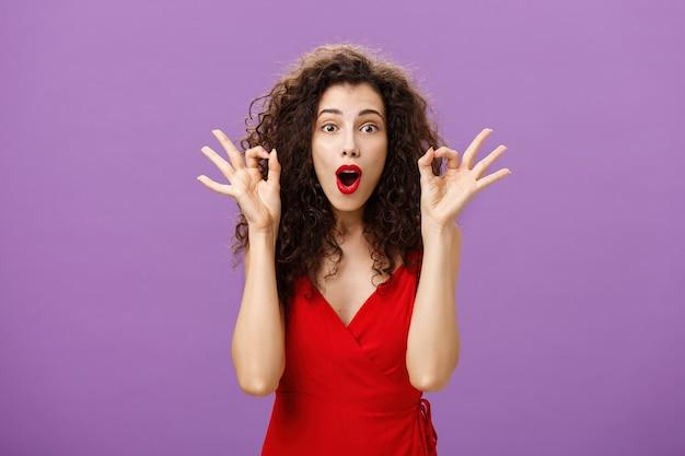 Femme assring mari qu'il fait très bien pour le soutenir pendant le match de poket debout étonné et excité sur un mur violet dans une jolie robe rouge montrant un signe correct ou excellent, pliant les lèvres d'excitation.