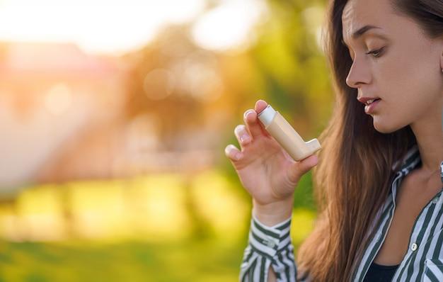 Femme asthmatique utilisant un inhalateur d'une crise d'asthme en plein air