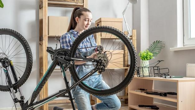 Une femme de l'atelier démonte son vélo et le répare. concept d'entretien et de préparation pour la nouvelle saison