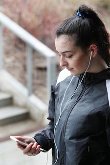 Femme athlète à la recherche de son smartphone