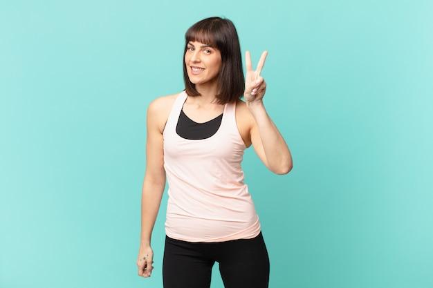 Femme athlète souriante et semblant heureuse, insouciante et positive, gesticulant la victoire ou la paix d'une seule main