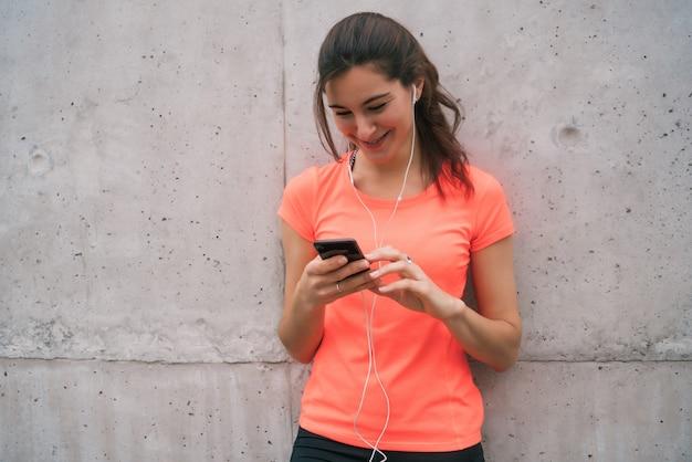 Femme athlétique à l'aide de son téléphone.