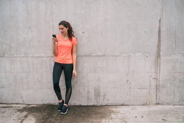 Femme athlétique à l'aide de son téléphone