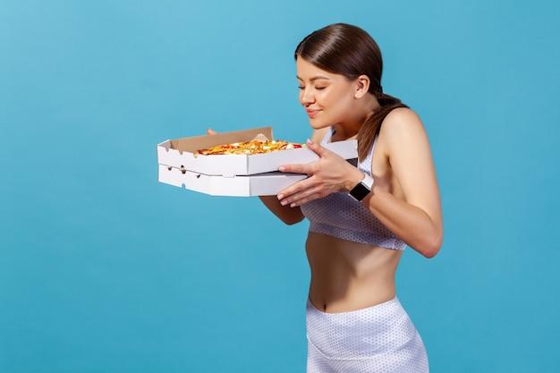 Femme athlétique appréciant l'arôme tenant dans les mains une boîte avec une pizza en évitant la malbouffe