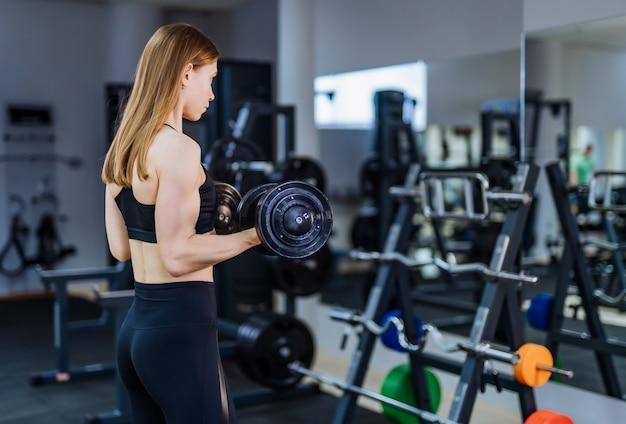 Femme athlétique aux cheveux longs, pompant des muscles avec des haltères devant le miroir du gymnase.