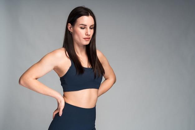 Une femme athlétique aux cheveux noirs en tenue de sport s'est concentrée de côté pendant qu'elle faisait une pause après un entraînement cardio. fille regardant pensivement au loin