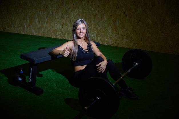 Femme athlétique blonde sexy dans un legging noir serré qui lève le poids dans le gymnase