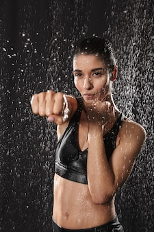 Femme athlétique caucasienne portant un soutien-gorge de sport noir avec un poing fermé, isolé sur fond de gouttes de pluie