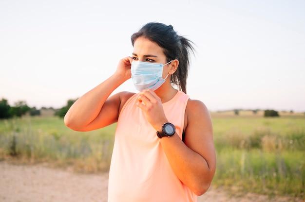Femme athlétique couvrant sa bouche et son nez avec un masque dans la rue
