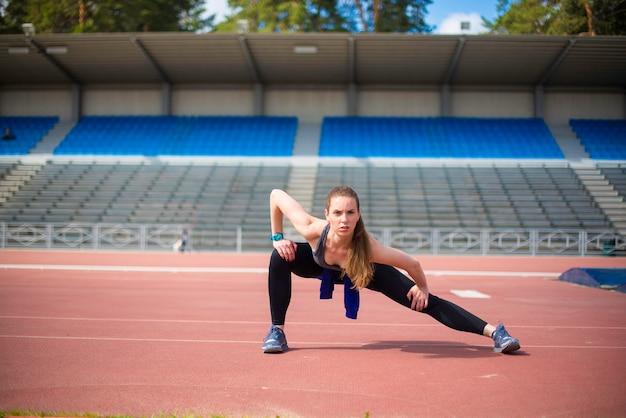 Femme athlétique étirant ses muscles avant de faire du jogging sur la bonne voie
