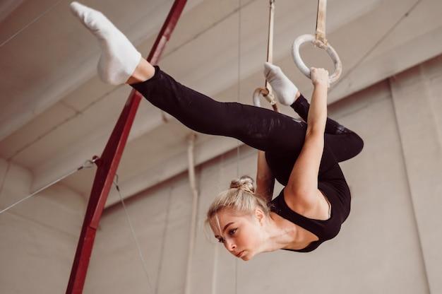 Femme athlétique à faible angle de formation sur les anneaux de gymnastique