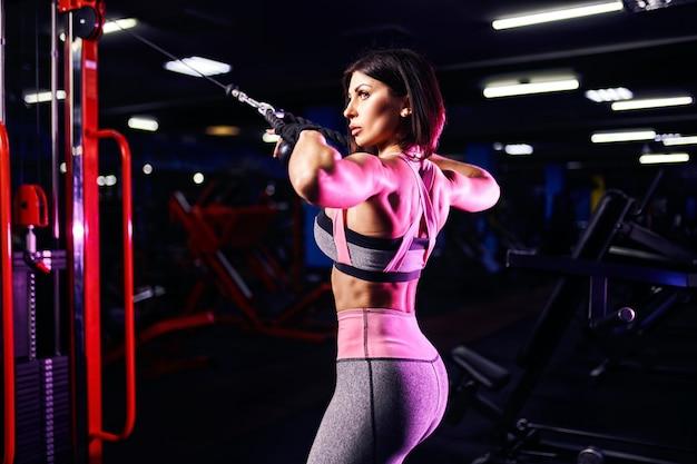 Femme athlétique, faire de l'exercice pour le dos, à l'aide de la machine, dans la salle de gym - vue arrière