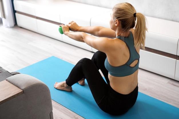 Femme athlétique faisant des exercices d'entraînement d'haltères à la maison