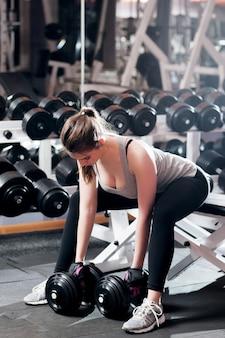 Femme athlétique faisant des exercices forts dans la salle de gym
