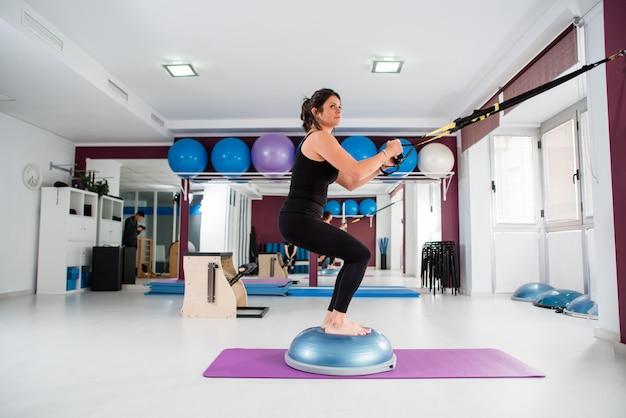 Une femme athlétique fait l'exercice trx