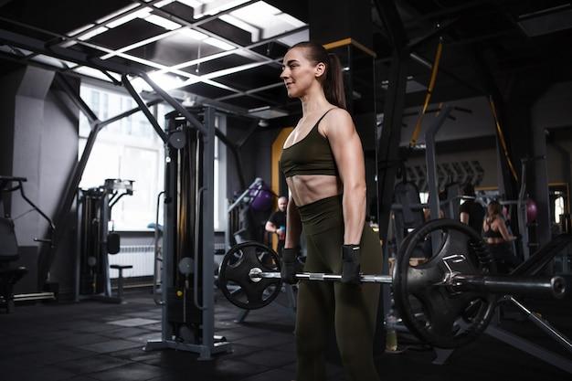 Femme athlétique forte soulevant des haltères lourds à la salle de sport, espace copie